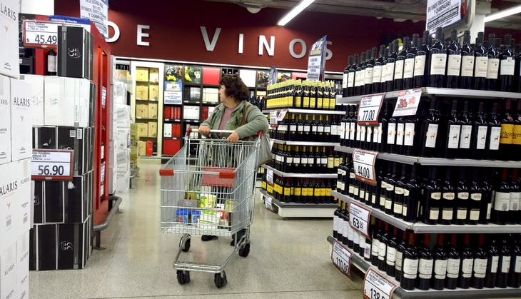 A woman pushes a trolley inside a supermarket offering bottles of wines in Buenos Aires, Argentina June 19, 2015. Just last year, Argentina was grappling with recession, inflation running at around 40 percent and a nose-dive in the black-market peso. On top of that came one of the biggest crises of President Cristina Fernandez de Kircher's presidency at the start of this year when a state prosecutor who accused her of criminal behavior was found dead. Yet voters' memories are short, say political analysts, and the success of the government's unorthodox measures to stabilize the economy and boost consumption is giving it a lift in popularity. Picture taken June 19, 2015. REUTERS/Enrique Marcarian  - RTX1HMO5