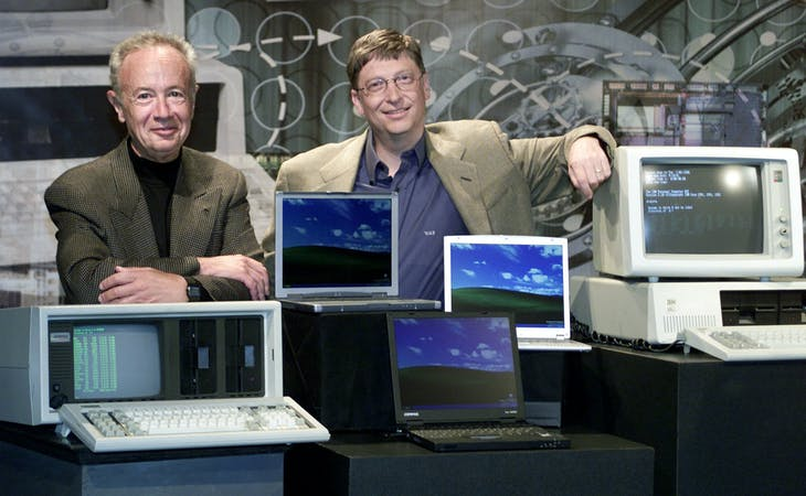 Bill Gates (R), chairman and chief software architect of Microsoft, poses for photographers with Andy Grove, chairman of Intel Corporation, at the Tech Museum of Innovation in San Jose, California July 8, 2001. Gates and Grove are standing with two of the oldest computers on each end and three of the newest laptop computers in the center. The event was held to commemorate the 20th anniversary of the personal computer. - RTXKOH8