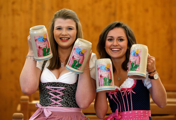 Model Sarah and Laura wear traditional Bavarian costume as they hold the official Oktoberfest beer mugs during a presentation in Munich, Germany August 23, 2016. REUTERS/Michaela Rehle /File Photo - RTX2N4V7
