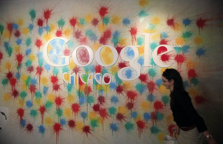 A woman walks past the Google Chicago headquarters logo in Chicago, March 20, 2012. REUTERS/Jim Young (UNITED STATES - Tags: BUSINESS SCIENCE TECHNOLOGY LOGO) - GM1E83L0CXJ01